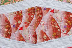 This red fabric with little birds is one of the last fabrics I have remaining from my fabric-buying rampage in Hawaii, years ago. I chose it for the color, and only realized later that there were birds.  Quilt story is at domesticat.net/quilts/sea-and-sky