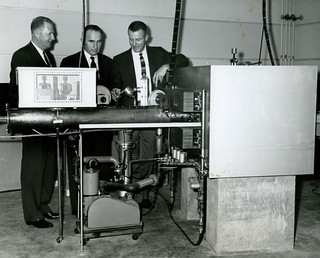 President E. Wilson Lyon, Trustee Frank Seaver 1905, and Physics Professor Edward Fryer examine the vitals of a Cyclotron being constructed for Pomona College in 1960 by Hughes Aircraft Company