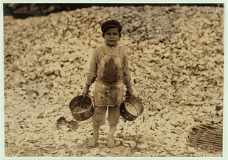 Manuel, the young shrimp-picker, five years old, and a mountain of child-labor oyster shells behind him. He worked last year. Understands not a word of English. Dunbar, Lopez, Dukate Company.  Location: Biloxi, Mississippi. (LOC) | by The Library of Congress