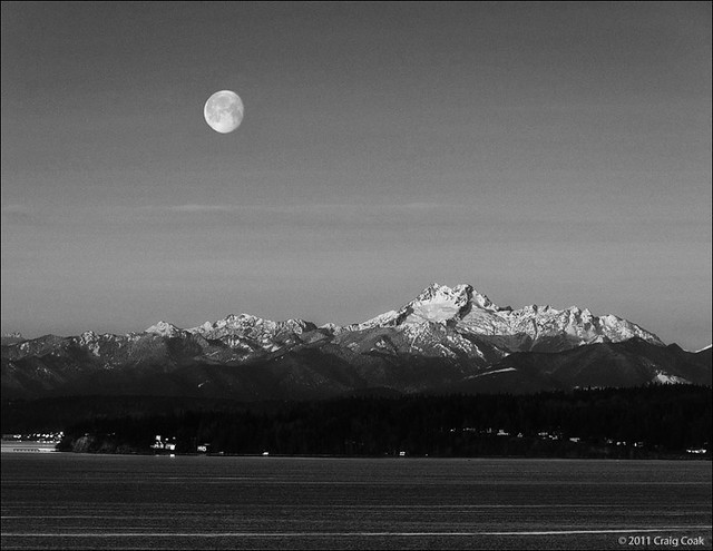 full moon setting over Olympic Mountains