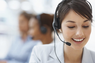 Smiling call center employee during a telephone conversation | by billyaustindallas