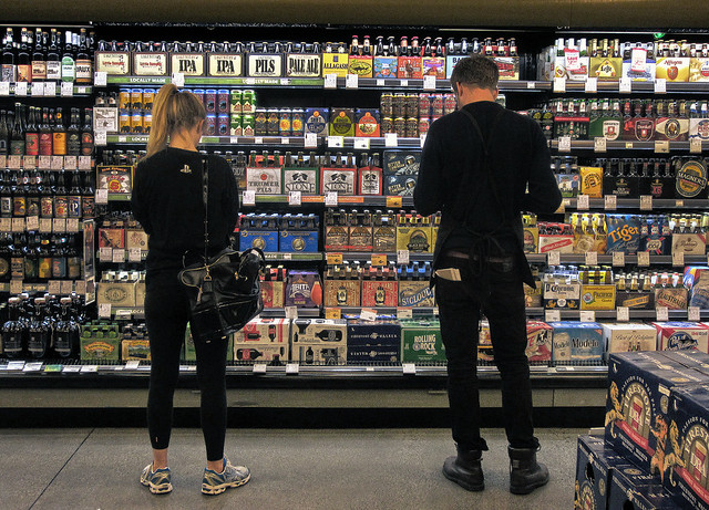 buyer and customer at the beer wall.  Whole Foods, San Francisco (2012)