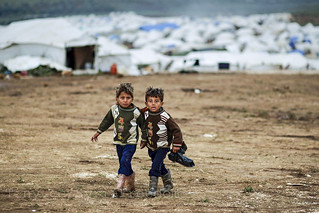 Syrian boys, whose family fled their home in Idlib, walk to their tent, at a camp for displaced Syrians, in the village of Atmeh, Syria, Monday, Dec. 10, 2012 | by FreedomHouse