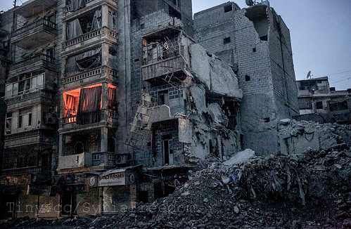 Night falls on a Syrian-rebel controlled area on Sa'ar street. An apartment is illuminated by fire used by one family to keep them warm beside destroyed buildings, among those the Dar Al-Shifa hospital, after airstrikes targeted the area last week, in Ale | by FreedomHouse