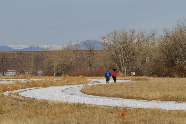 Walkers enjoy Cherry Creek State Park with Long's Peak in the background...