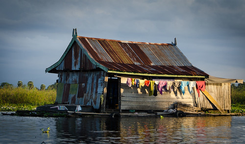 Tempe lake floating house with colourful clothes drying   by Jerome Nicolas