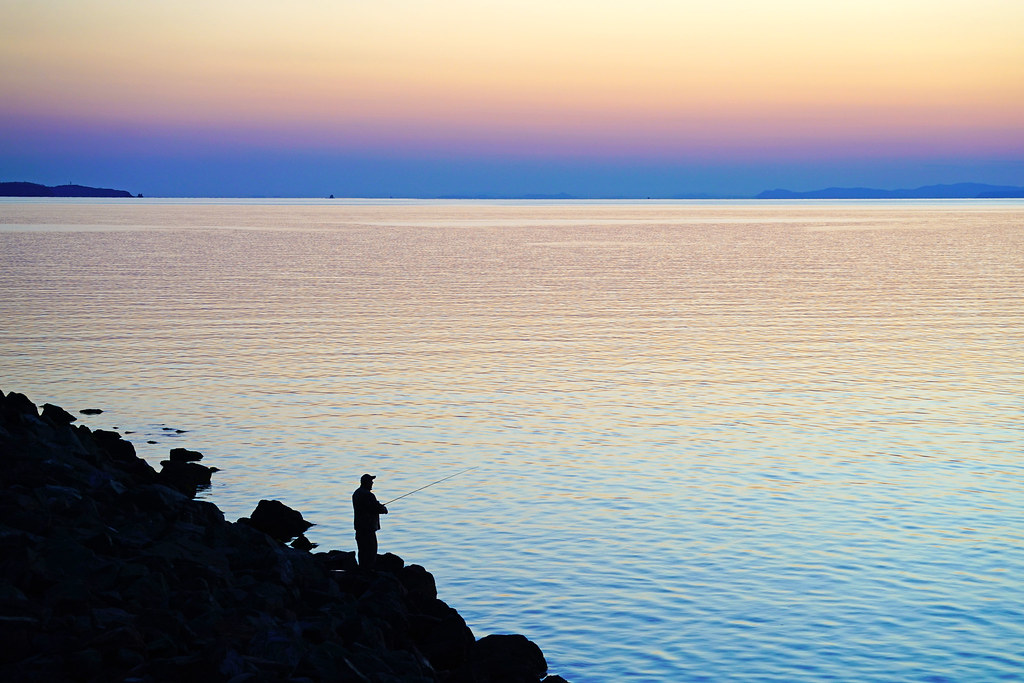 Fisherman at the seashore after sunset, Vladivostok, Russia