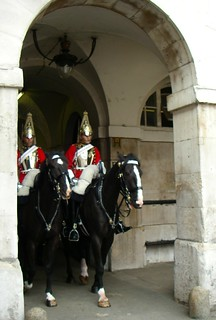 Changing of the guard, riding through the arch, British soldiers mounted on horseback, red coats, metal helmets, white saddle cloth, London, England, UK