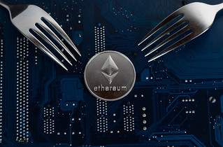 Ethereum coin with forks on motherboard | by wuestenigel
