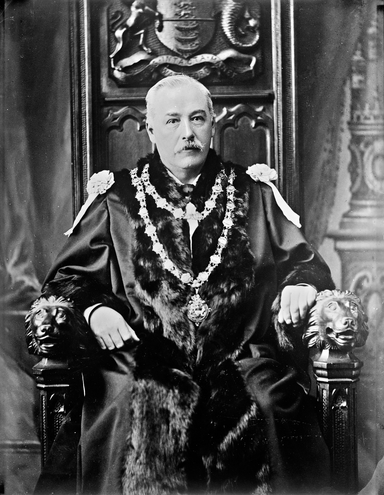A distinguished gentleman in robes and chain of office sitting on a throne (of sorts)
