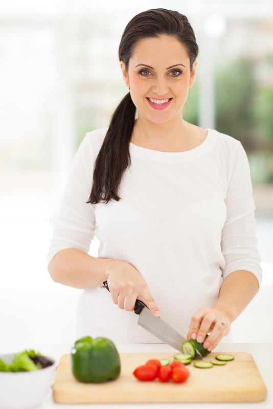 portrait of pregnant woman cutting vegetables