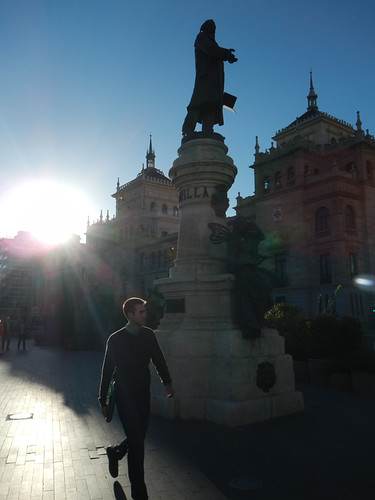 The sun flares around a walker in Valladolid, Spain