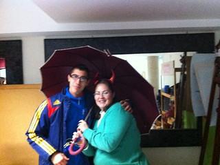 Jose le entrega el paraguas a Lourdes.