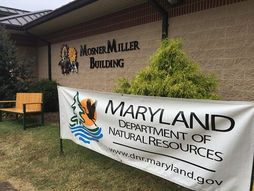 Photo of exterior of Miller Mosner Buildling at Maryland State Fairgrounds, with Maryland DNR banner