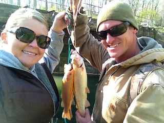 Photo of a woman and man holding up a pair of golden trout