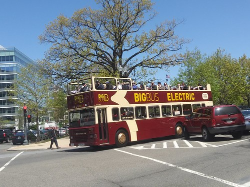 An open air double deck tourist bus (BigBus) with riders up top on Louisiana Avenue NE near Union Station