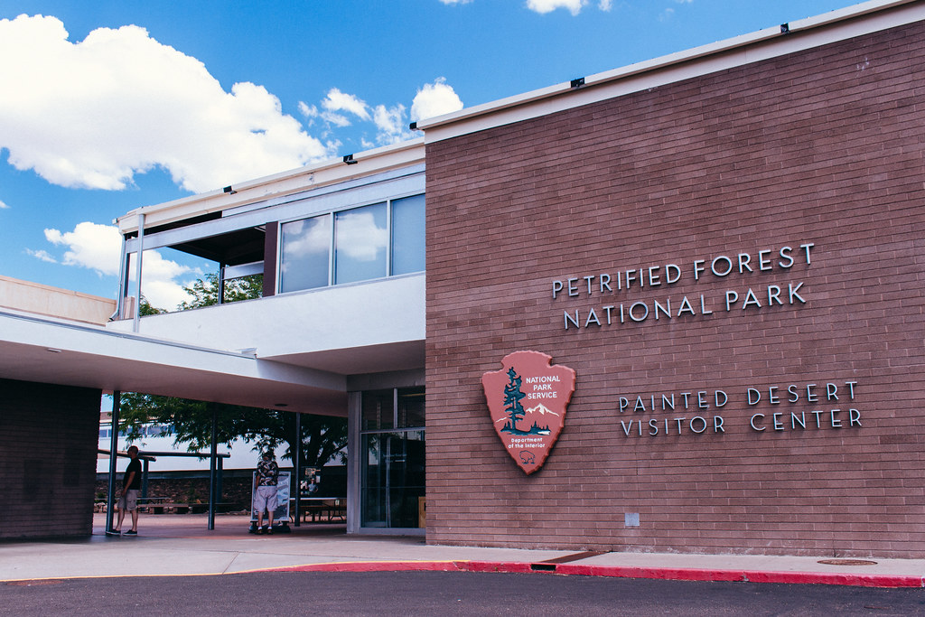 Mid-century modern two-story building with national park logo on the wall