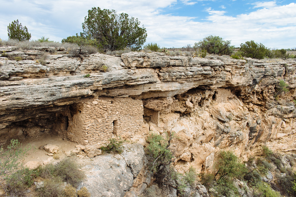 Stone dwellings are built into weathered limestone cliffs upon which juniper trees grow