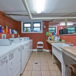 Bright red accent walls brightens up your laundry days.