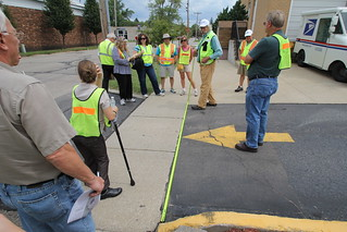 Walkability Expert Dan Burden Measures Parking Lot Entrances During a Walking Audit in Paw Paw Michigan