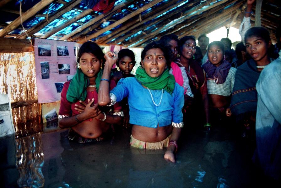 women waist-deep in water protesting dam
