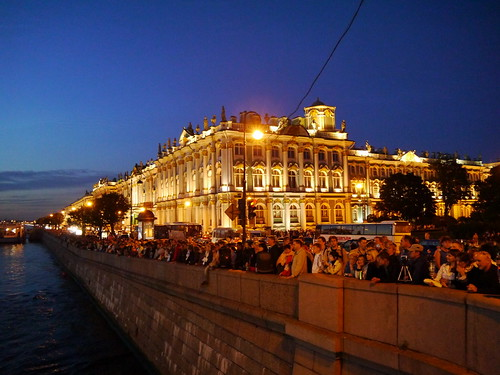Crowd along the Neva River waiting for the Palace Bridge to be drawn. State Hermitage Museum in the background
