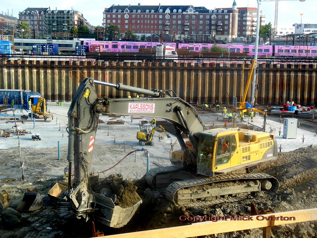 Pink wrap S train passes Volvo EC460B digger at work on IKEA site