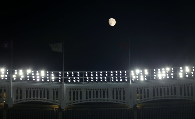 The Moon is in a Waxing Gibbous phase over the Yankee Stadium facade.