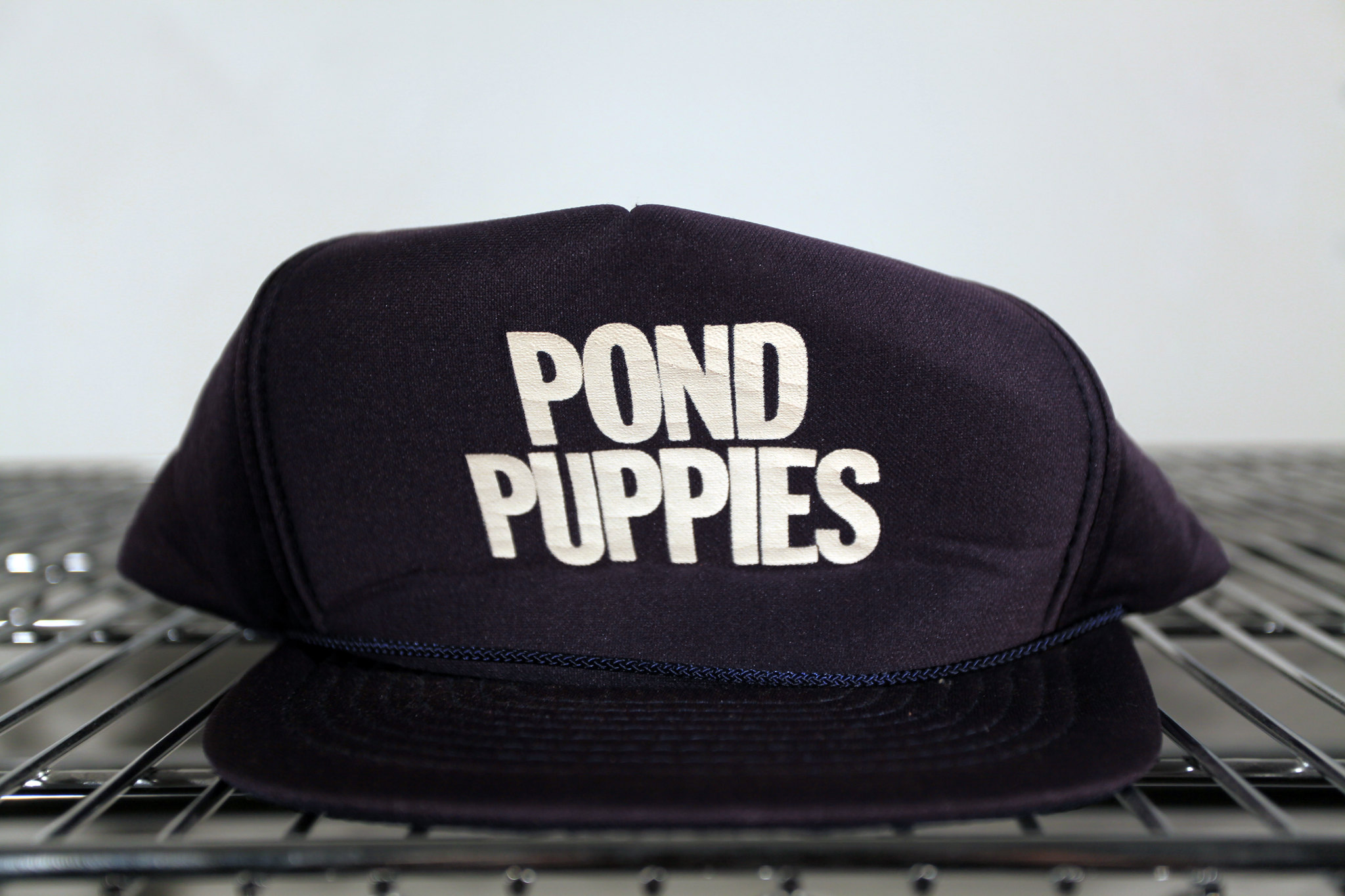 Closeup of a navy blue baseball cap with the words Pond Puppies in white, sans serif, all-caps letters.