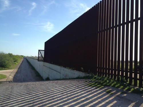 <p>Bollard fencing around a flood canal is a second line of defense in south Texas.</p>