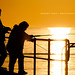 Silhouette of couple fishing on jetty, Australia by Robert Lang Photography