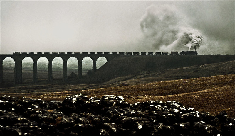 The wind and the rain are lashing across Batty Moss as Stanier class '8F' 2-8-0 No.48151 gets to grips and slowly moves off from Batty Moss viaduct with its heavy stone train, a Ribblehead sidings to Carlisle ballast crossing on Tuesday 19th December 2000. Very much a once-in-a lifetime opportunity for me, to photograph a steam-hauled freight on the Settle to Carlisle line, although I had witnessed them without a camera in the 1960s.  Railtrack chartered LMS Stanier-designed Heavy Freight 8F 2-8-0 No. 48151 from Carnforth, which took a train of 20 hoppers from Hellifield to Ribblehead for loading, then forwarded them to Carlisle in appalling weather. This trip was to mark the reopening of the Settle to Carlisle railway line after a major refurbishment.  A cropped Mamiya 645 ProTL Fuji Provia transparency taken with the 150mm lens. It came back from my local Harrogate processing laboratory with deep scratches in the film. I guess that a trained monkey could have processed the film better! Thanks to modern technology I have been able to restore it.  The earlier 45mm shot that I took with my other Mamiya (with Agfa Scala B&W transparency film loaded) is here: www.flickr.com/photos/12a_kingmoor_klickr/8436059666/in/s...  © Gordon Edgar - All rights reserved. Please do not use my images without my explicit permission
