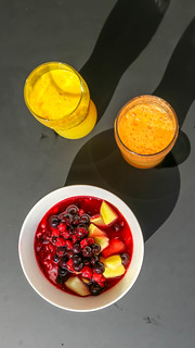 Two glasses of orange juice and a fruit salad with cherry, sour cherry, apple and water melon | by marcoverch