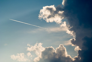 Jet emerging from behind the clouds | by Ivan Radic