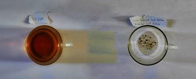 Left: tea - decoction Right: tea drunken, no more decoction in the tea cup, but sediment remains. links: Blick in den Teesud Rechts: ausgetrunken: Bodensatz jedoch kein Teesud, keine Patina, kein Kosmos im Teeglas - Licht, Schatten auf weißem Blatt Papier