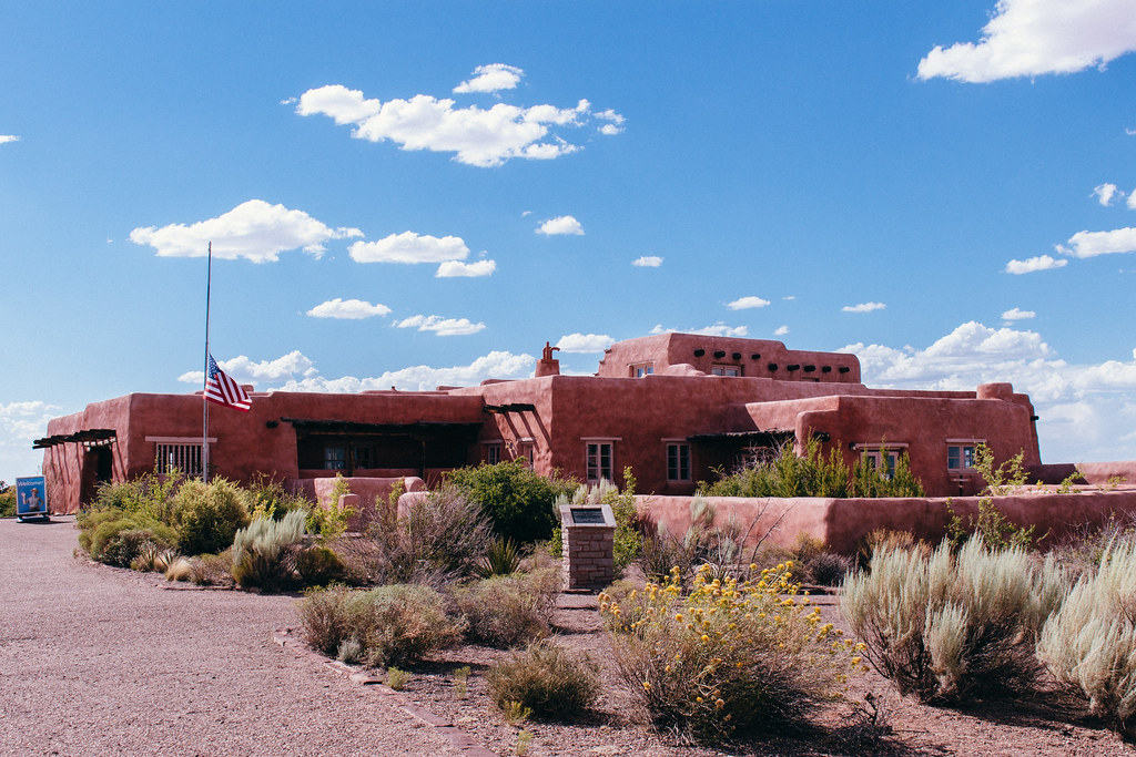 a Pueblo Revival style building with brush growing around it and clouds in a blue sky