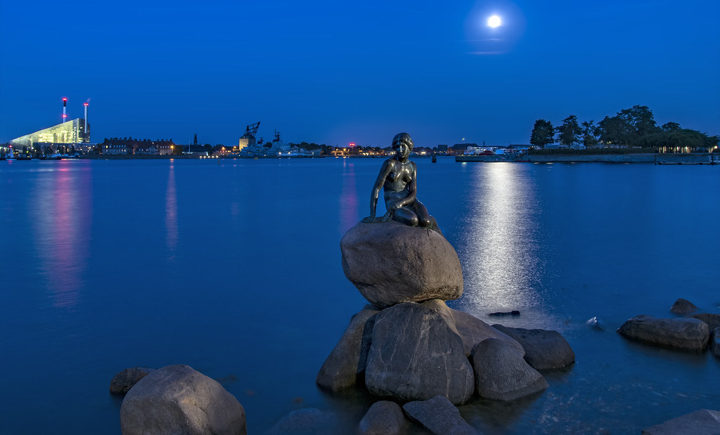 Copenhagen's Little Mermaid under a full moon during the blue hour