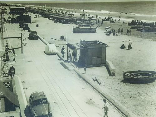 Platja de Calafell, 1950. Es veu un patí al fons rodejat de barques.