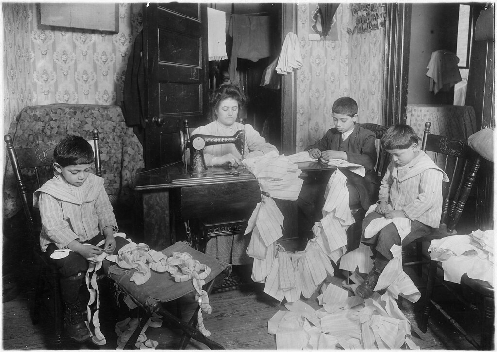 Making dresses for Campbell kids dolls in a dirty tenement. The older boy, about 12 years old, operates the machine when the mother is not using it. New York City, March 1912