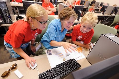 Sally Bilder and her grandchildren, Saskia and Martijn den Boon, program an interactive computer game during a Grandparents University class.