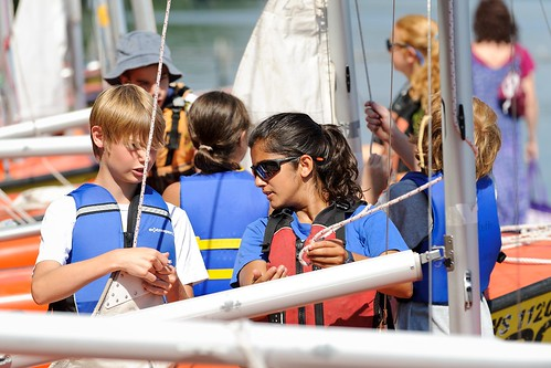 Undergraduate student Tulika Singh, right, helps a young student learn to rig a sailboat