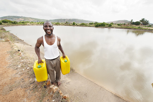 Man fetching water from a reservoir in the Central Region Tuba Irrigation Scheme in Ghana.