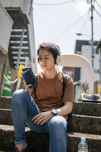 Young man listening to music on street