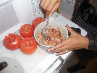 Teen preparing stuffed tomatoes   by Lyn Lomasi