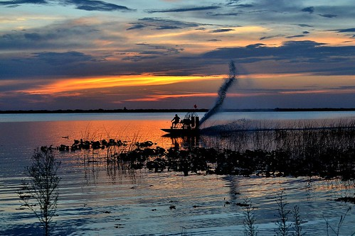 sunset sky sun lake water clouds boat