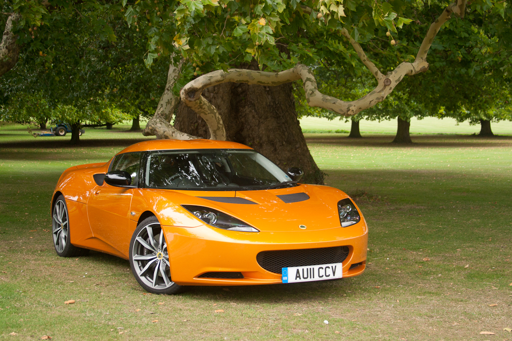 An orange Lotus Race car is pictured in front of a tree