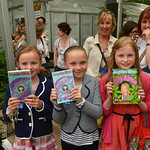 Three happy readers | Three young readers happily clutch their books