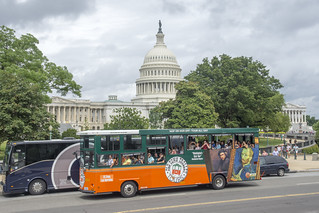 Tour buses pass the U.S. Capitol on a cloudy day