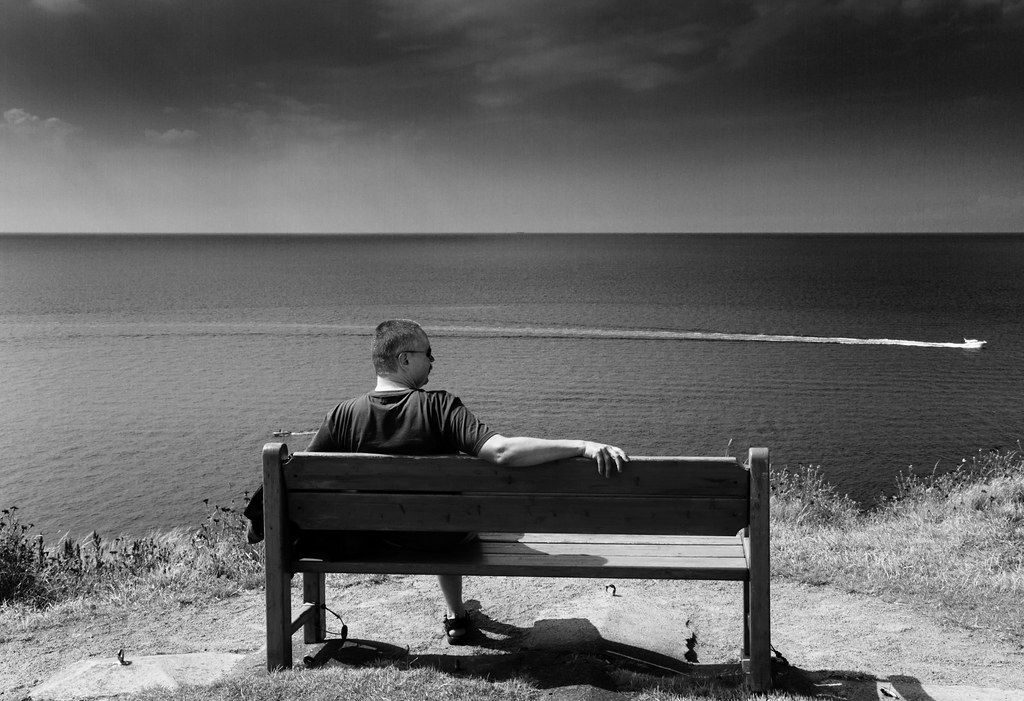 On a bench before the sea