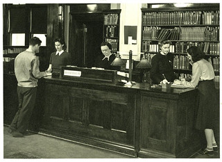 Students checking out materials at front desk of Carnegie Library circa 1950. Librarian Mary Love is at center.